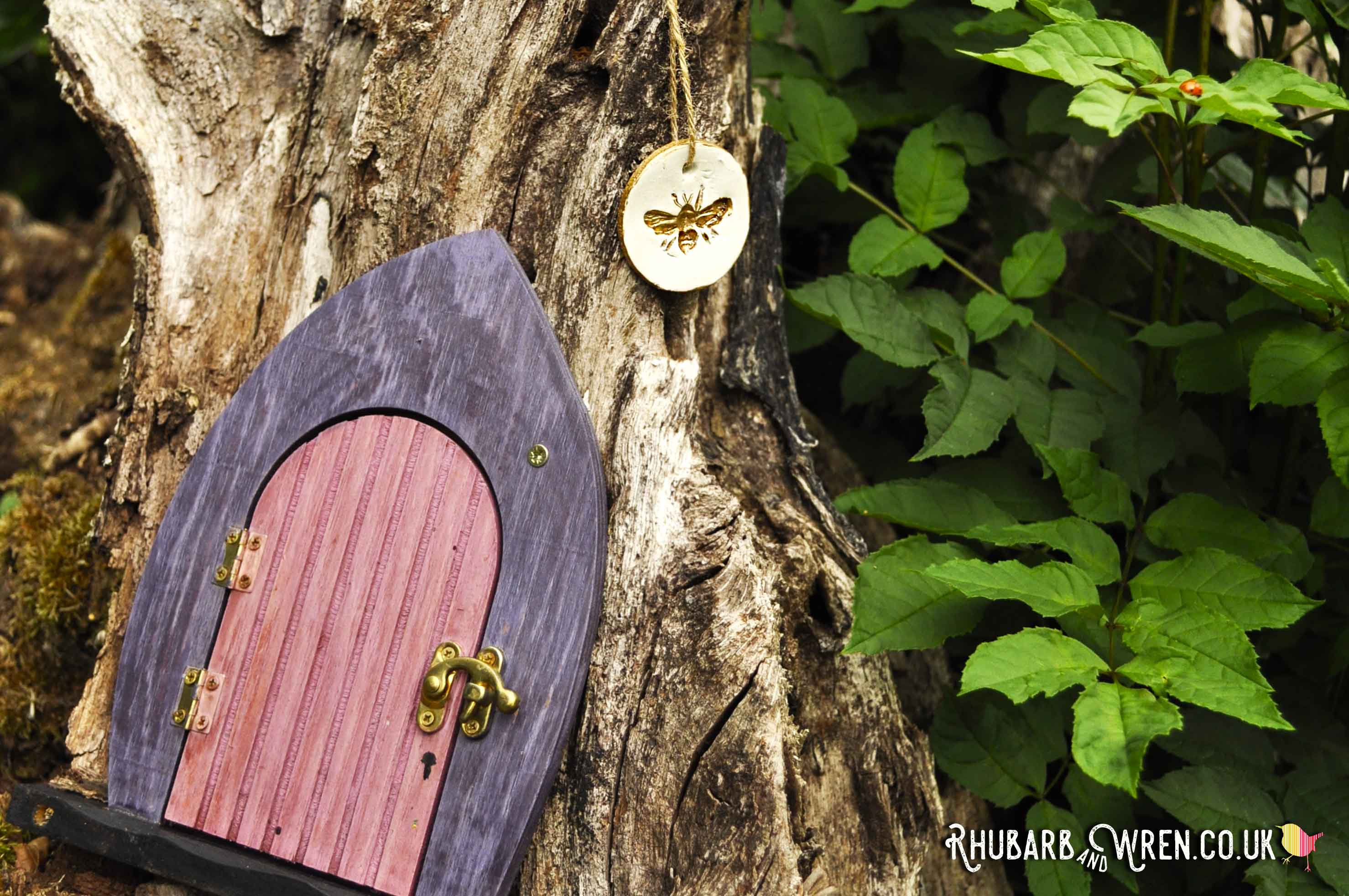 Bee pendant hidden by a fairy door for a kids treasure hunt in the woods