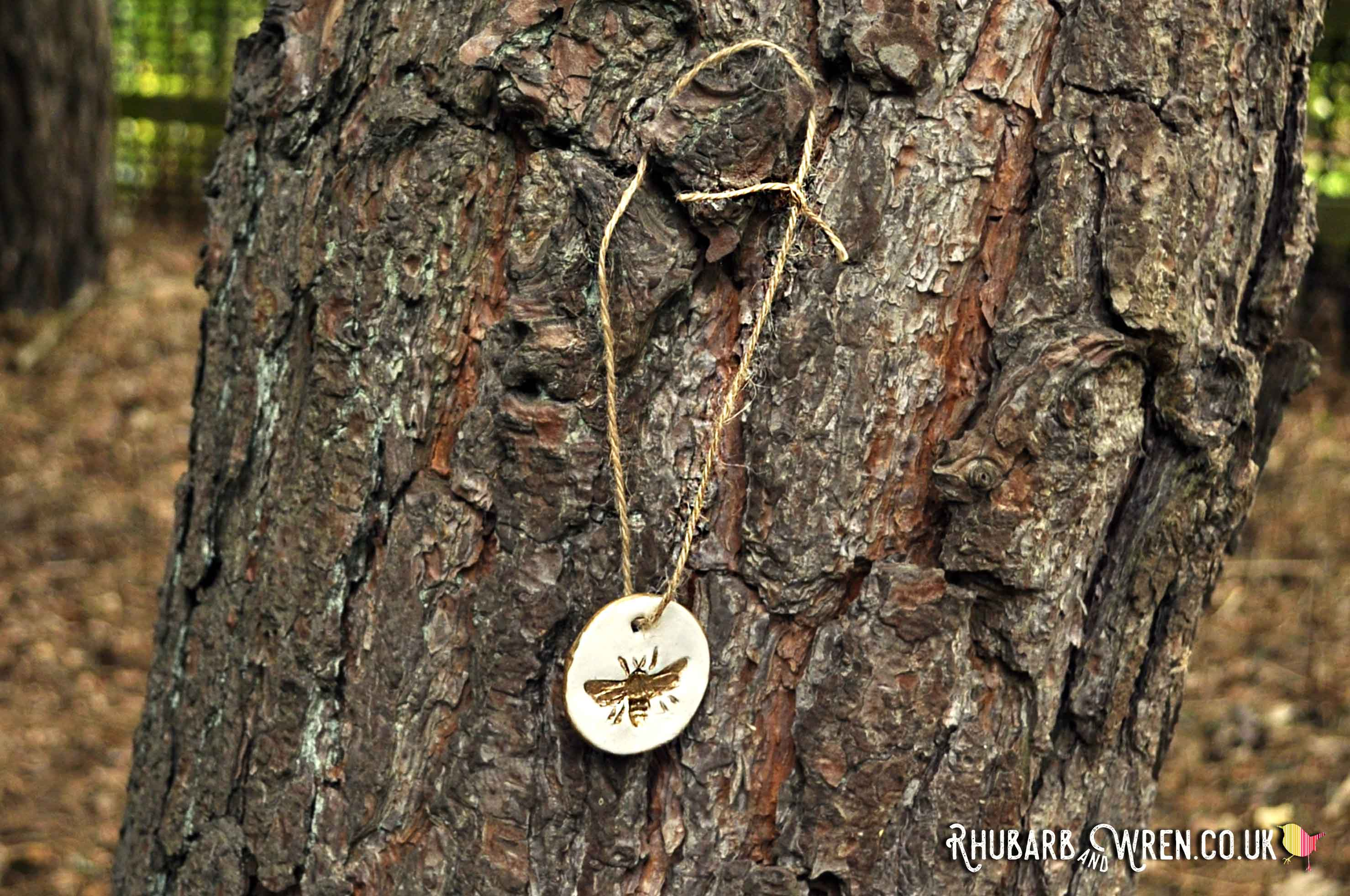 Bee pendant for kids treasure hunt hanging on gnarly bark of a tree