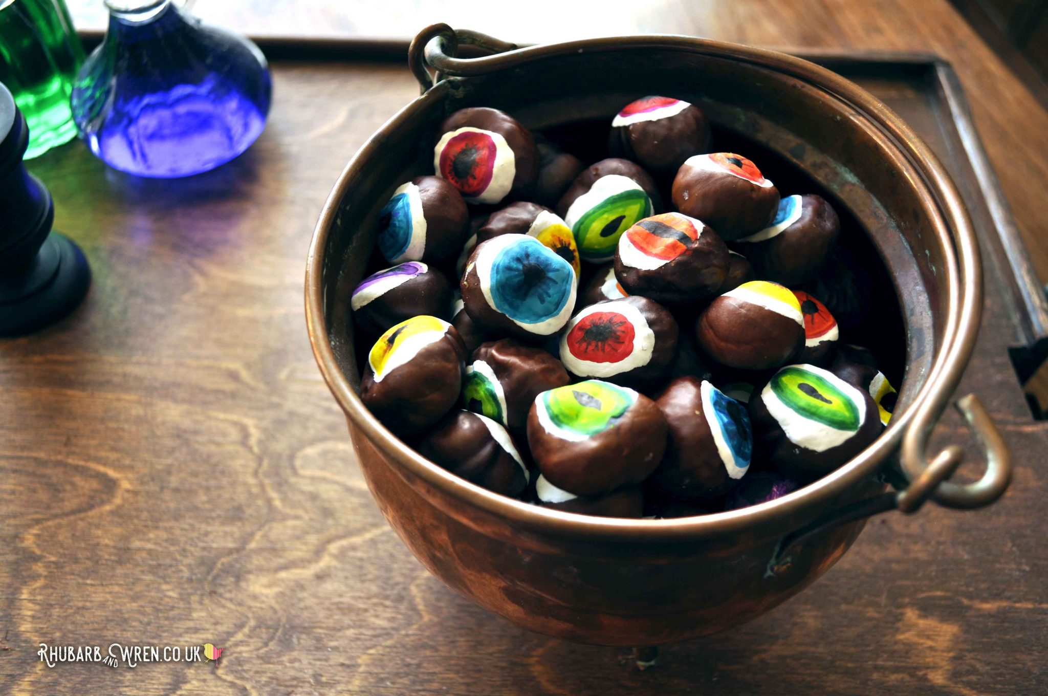 Cauldron full of DIY conker eyeballs for a fun kids Halloween activity.