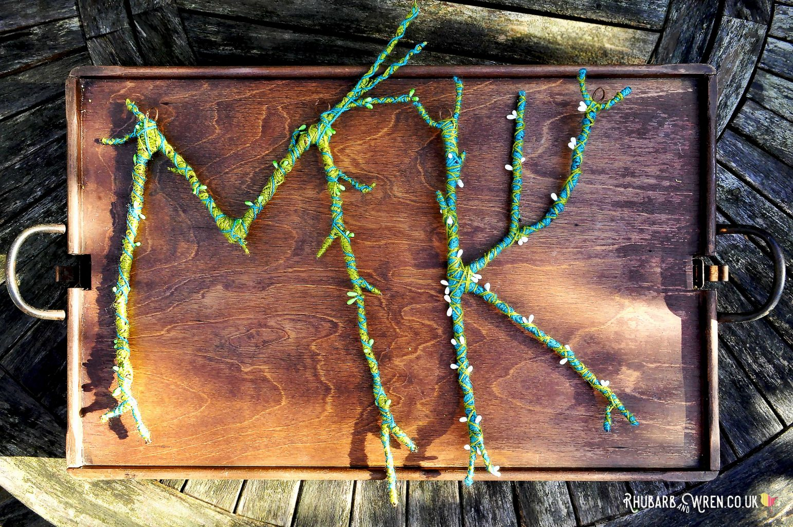 DIY twig letters wrapped in contrasting colour wool/yarn and decorated with pip berries