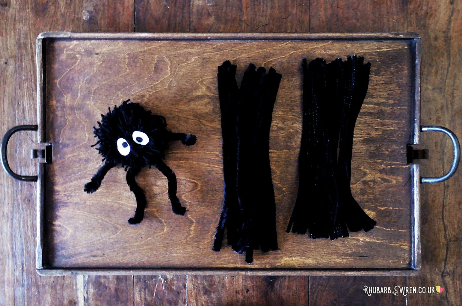 A pompom with pipecleaners for arms and legs.