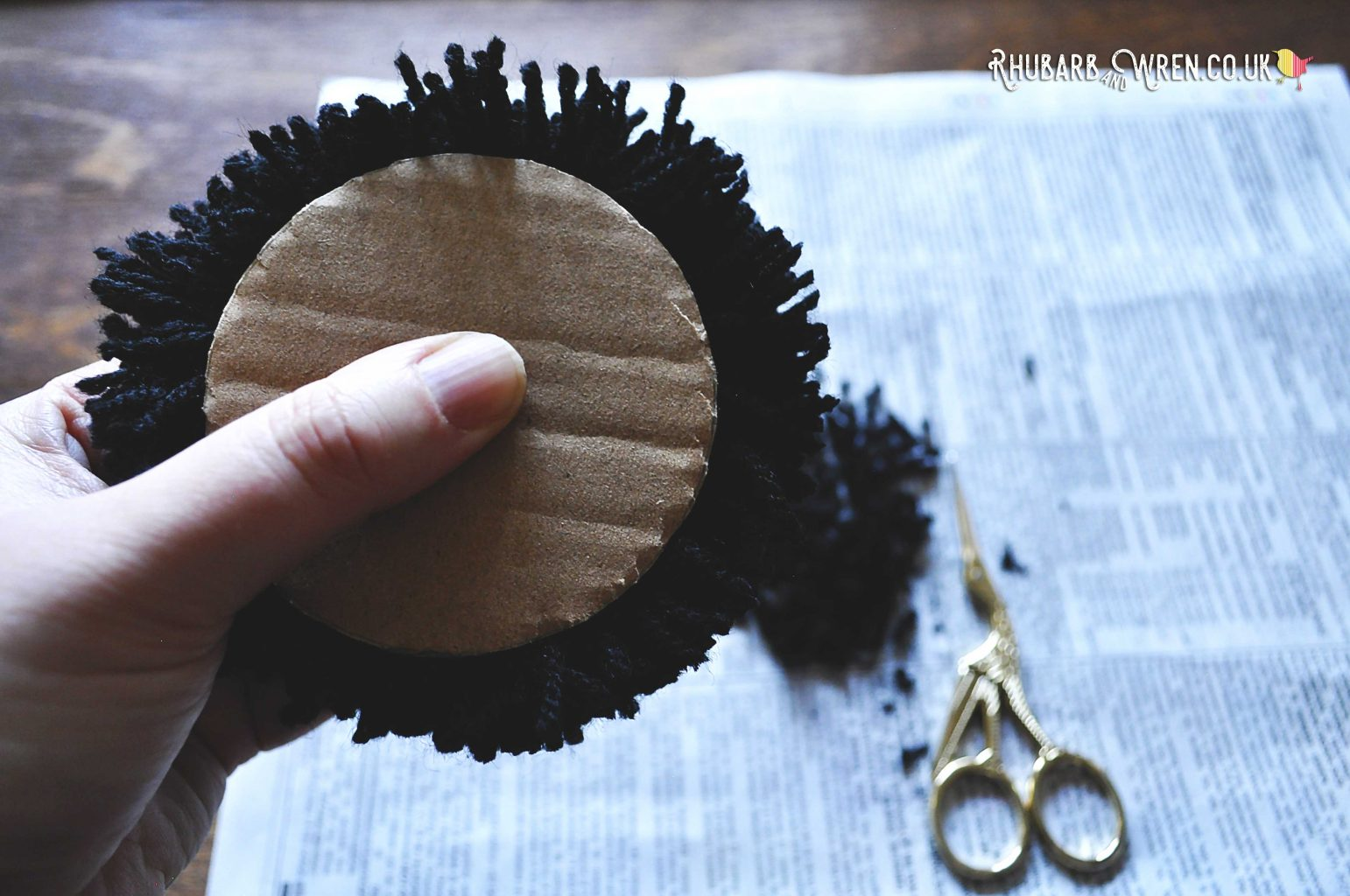 A pompom sandwiched between two circles of cardboard, to be trimmed into a perfect sphere.