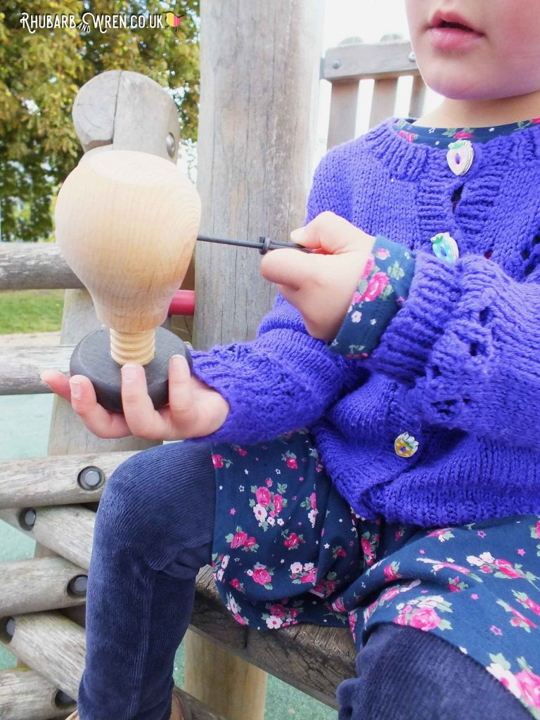 Preschooler using a drill and vice to make holes in conkers