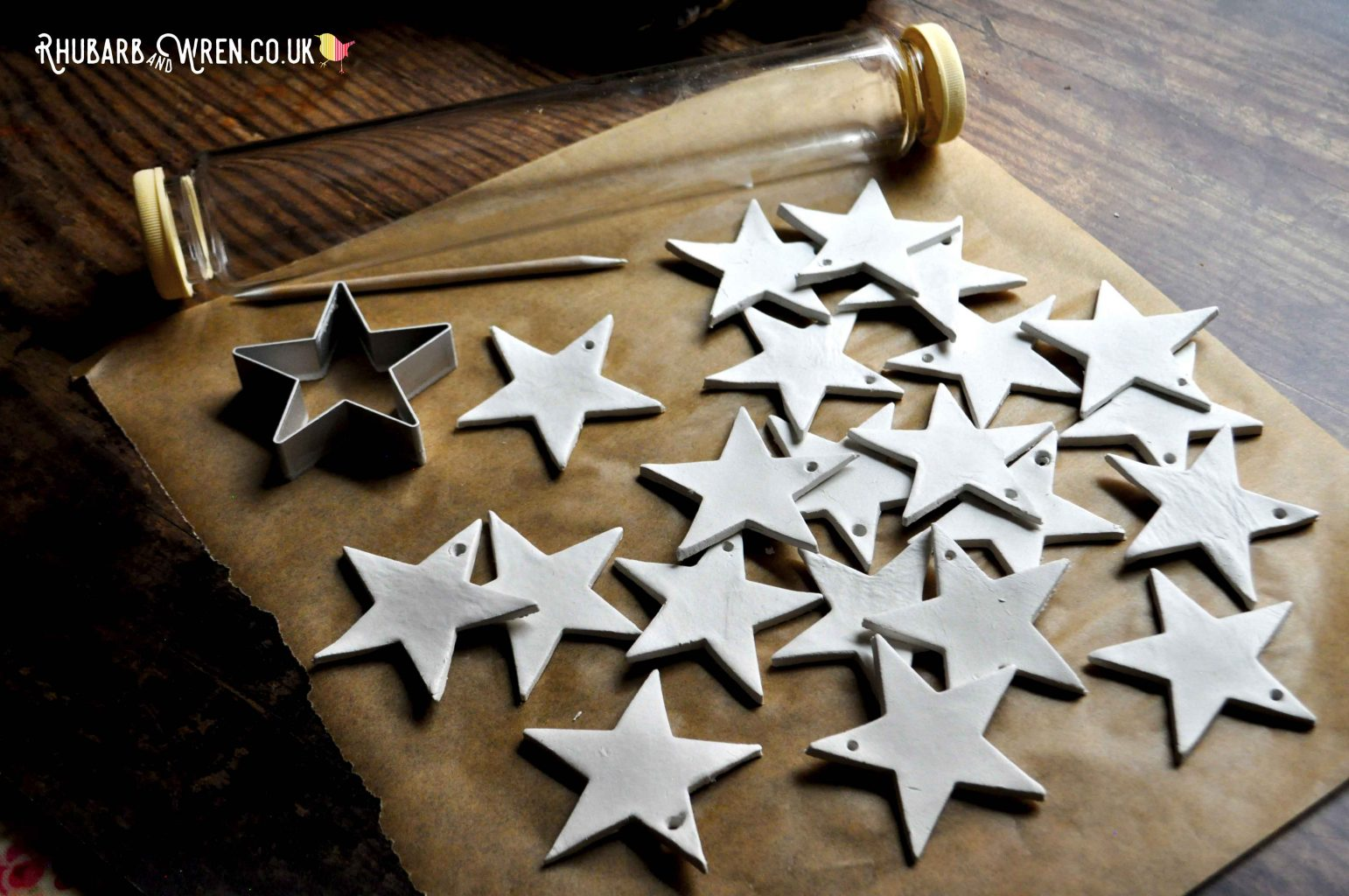 Using a glass rolling pin and star biscuit cutter to make clay star ornaments for Christmas decorations.